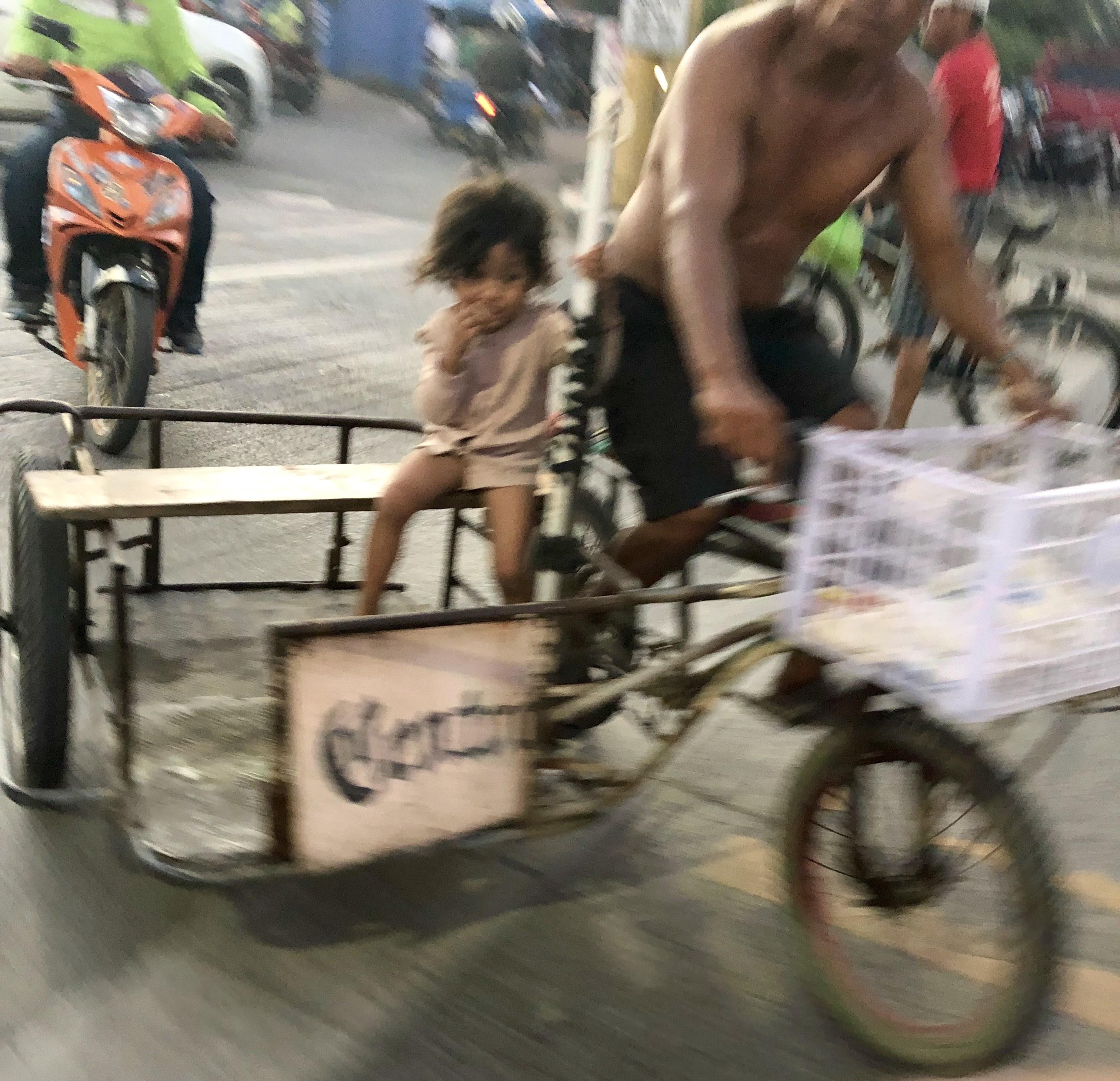 Petite fille dans un side velo a Cebu. Pollution et misère
